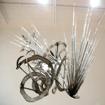 "2012_""Autonomy"", aluminum, steel forks, glass test tubes, glass pipettes, feathers, spray paint, 2' diameter. (c)Vera Gould."