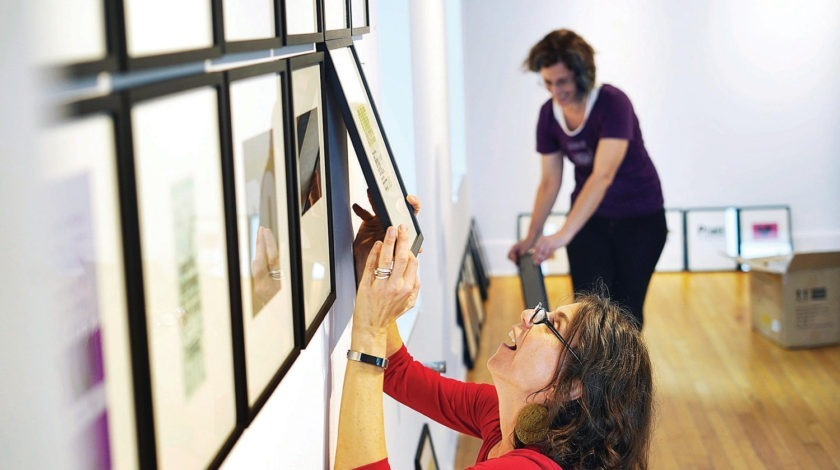 "BEN GARVER — THE BERKSHIRE EAGLE Artist Melanie Mowinski hangs examples from her ""50 Card Project"" in the ""Showing Up: for Our Communities, Our Neighborhoods and Our Selves"" exhibit at the Lichtenstein Center for the Arts in Pittsfield."